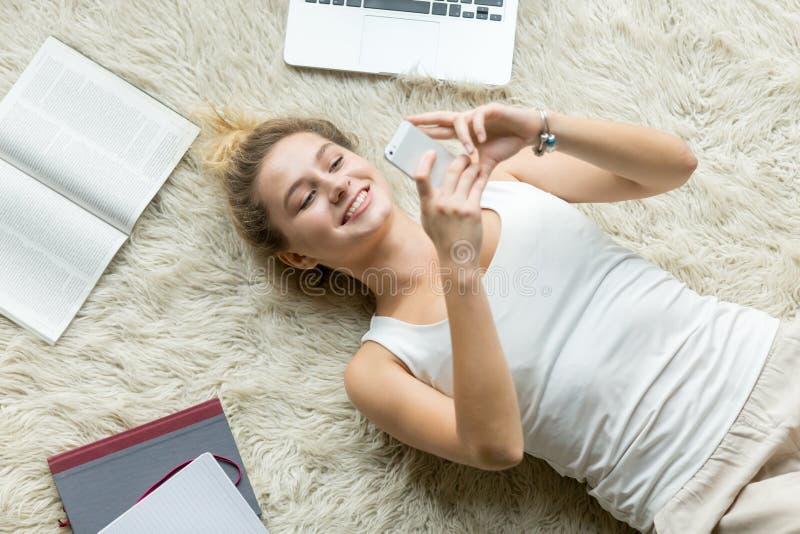 Bästa sikt av messaging för ung kvinna på telefonen hemma arkivbilder