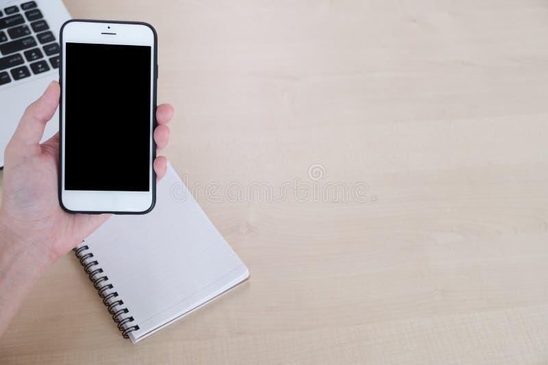 Bästa sikt av mobiltelefonen för kvinnahandbruk på tabellen, den tomma boken och bärbar datorbakgrunden, kopieringsutrymme royaltyfri bild