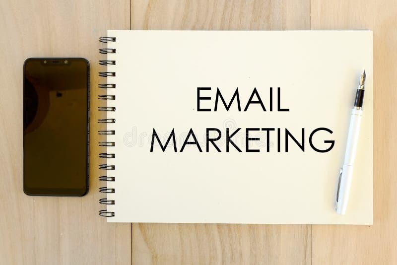 Bästa sikt av mobiltelefonen, pennan och anteckningsboken som är skriftliga med Emailmarknadsföring på träbakgrund royaltyfria foton