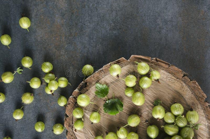 Bästa sikt av mogna krusbär på träyttersidan, grå tabell royaltyfri fotografi