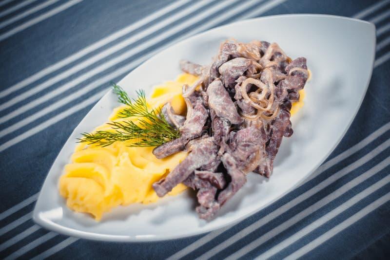 Bästa sikt av nötköttStroganoff med mosade potatisar på en vit platta Platta på tabellen med en blå bordduk i vit fotografering för bildbyråer