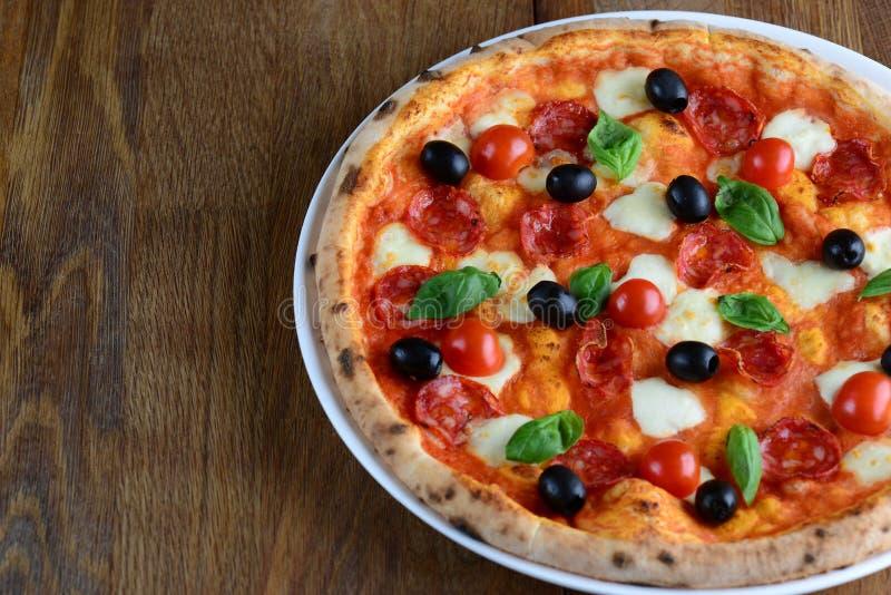 Bästa sikt av neapolitan pizza med peperonin, mozzarellaen, körsbärsröda tomater och svarta oliv på en trätabell close upp Makro arkivbild