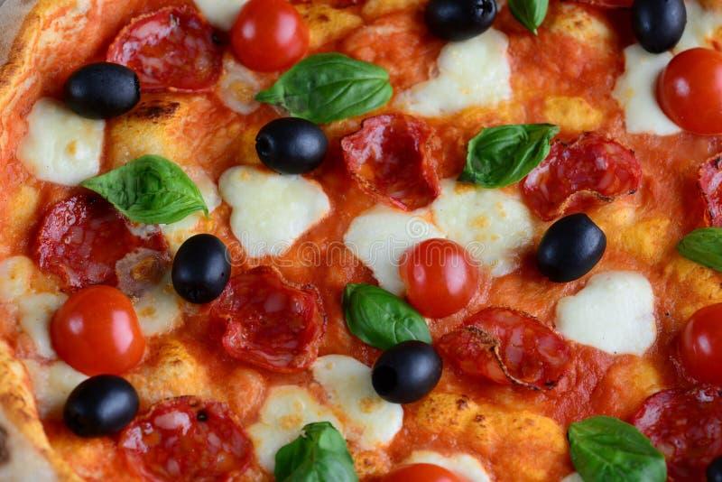 Bästa sikt av neapolitan pizza med salami, mozzarellaen, svarta oliv och basilika close upp Makromatbakgrund arkivbild