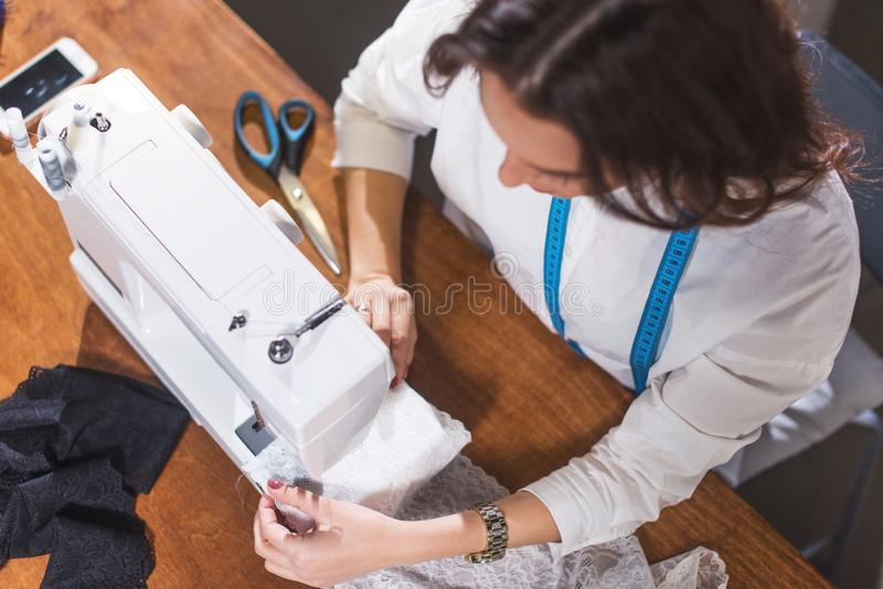 Bästa sikt av needlewomanen som syr tyg på symaskinen på arbetsplatsen i studio royaltyfria foton