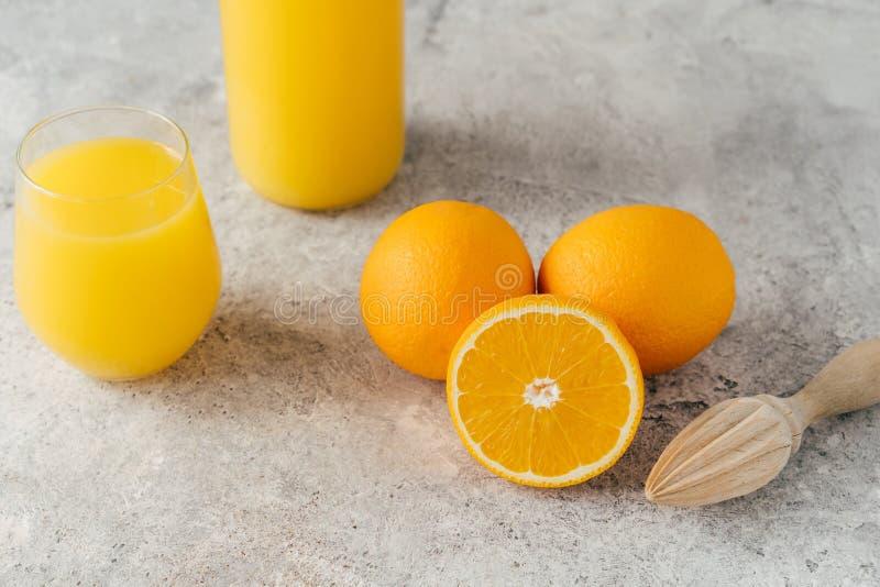 Bästa sikt av nya apelsiner och ny orange fruktsaft i exponeringsglas, träjuicer på den vita tabellen Multifruit fruktsaft Fruktd arkivfoton