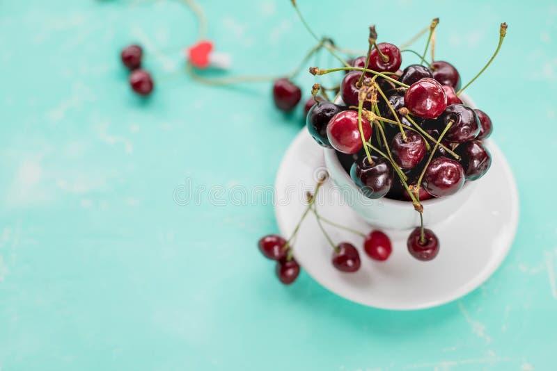 Bästa sikt av nya röda körsbär i en vit kopp, på azur bakgrund Sunt banta, viktförlust eller hälsningsommarbegreppet royaltyfri fotografi