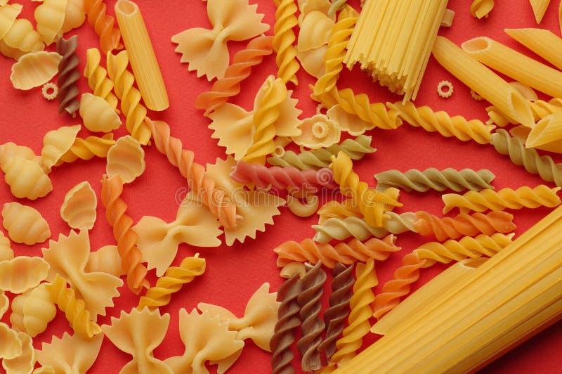 Bästa sikt av okokt italiensk pasta som isoleras på apelsinen Olika typer av pasta, makrosikt arkivbilder