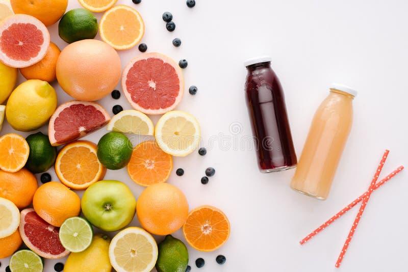 bästa sikt av olika citrusfrukter och blåbär med flaskor av fruktsaft royaltyfria foton