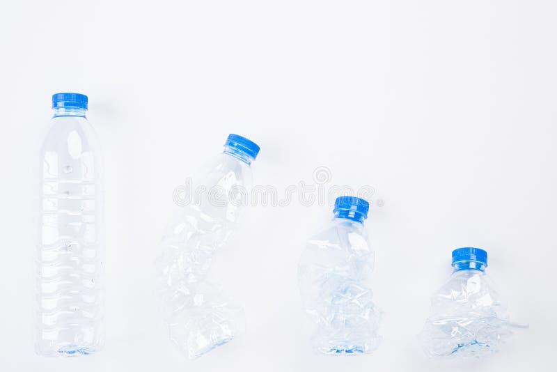Bästa sikt av olika tomma plast- vattenflaskor från fullt till krossat på vit bakgrund Återanvänd, dagen för världsmiljön och Eco arkivbild