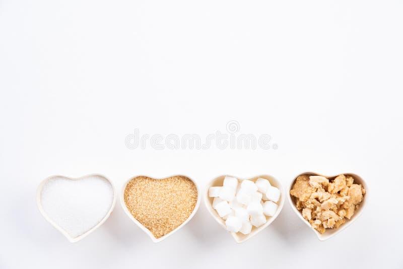 Bästa sikt av olika typer av socker Bitsocker, farin för rått socker och strösocker i hjärtabunke på vit bakgrund plant arkivbild