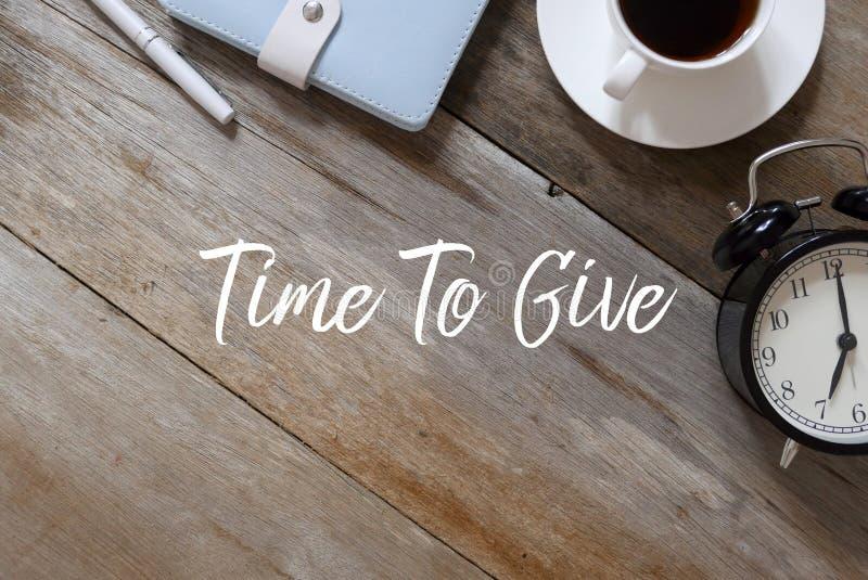 Bästa sikt av pennan, anteckningsboken, kaffe och klockan på träbakgrund som är skriftlig med Tid som ska ges arkivbild