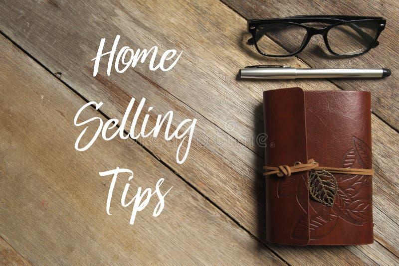 Bästa sikt av pennan, exponeringsglas och anteckningsboken på träbakgrund som är skriftlig med hem- spetsar för sälja royaltyfria bilder