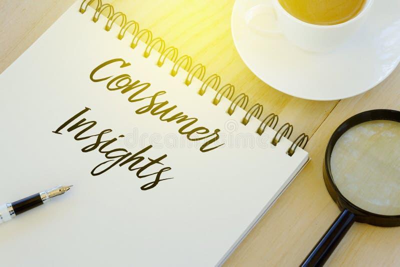 Bästa sikt av pennan, förstoringsglaset, en kopp kaffe och anteckningsboken som är skriftliga med konsumentinblickar på träbakgru royaltyfria bilder