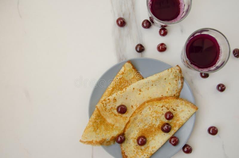 Bästa sikt av plattan med pannkakor och exponeringsglas med fruktsaft royaltyfri bild
