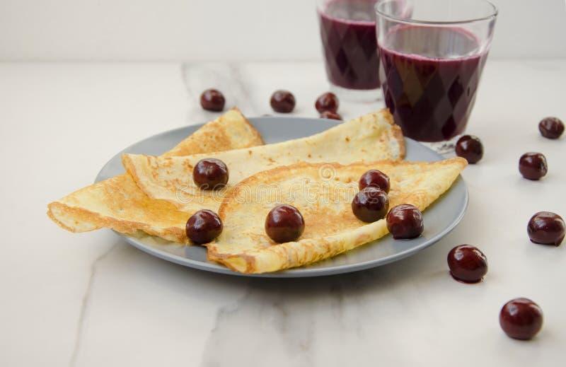Bästa sikt av plattan med pannkakor och exponeringsglas med fruktsaft royaltyfria foton