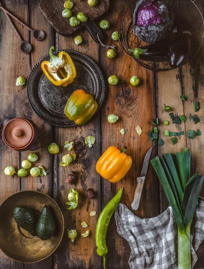 bästa sikt av purjolöken, peppar, avokadon, aubergine, brussel - groddar, röd kål, kökshandduk, kniv, plattor, skedar, skärbräda royaltyfri bild
