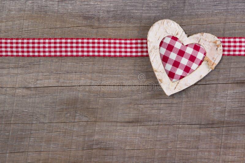 Bästa sikt av röd kontrollerad hjärtagarnering på träbakgrund - royaltyfria bilder
