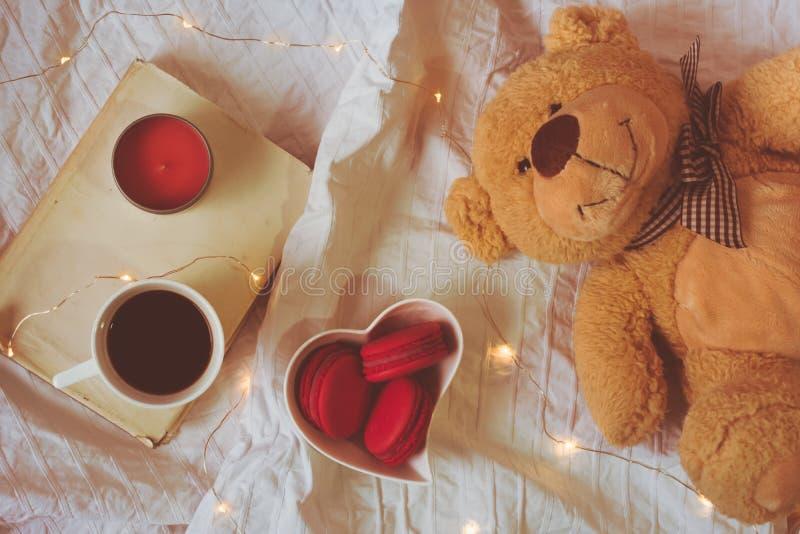 Bästa sikt av röda eller rosa macarons i en hjärta formad bunke, kaffe, bok, en stearinljus och en nallebjörn royaltyfri foto