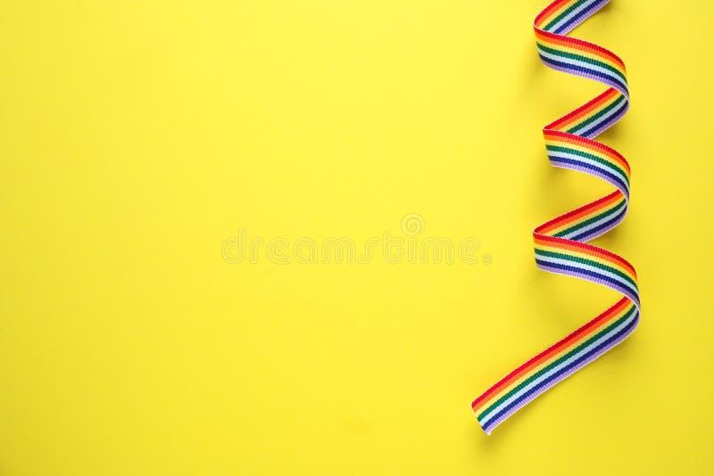 Bästa sikt av regnbågebandet på gul bakgrund glatt symbol fotografering för bildbyråer