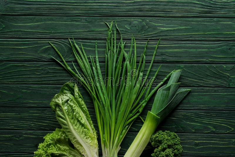 bästa sikt av salladslöken, purjolöken och persilja på trätabellen som är sund arkivfoto