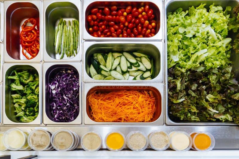 Bästa sikt av salladstången med sortimentet av ingredienser För sunt och att banta mål royaltyfri foto