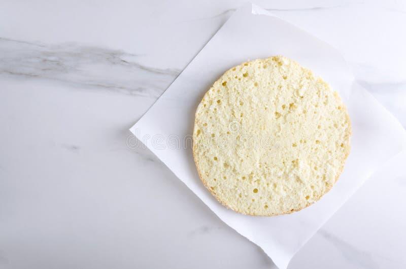 Bästa sikt av skivan av sockerkakan på det stekheta papperet vit marmorerar tabellen i köket fotografering för bildbyråer