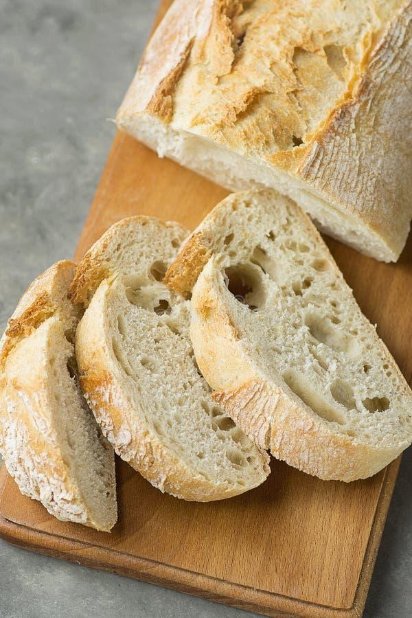 Bästa sikt av skivat Artisanal lantligt bröd på den trätabellen för skärbrädamörkerbetong Svampig Holey textur för guld- skorpa arkivbild