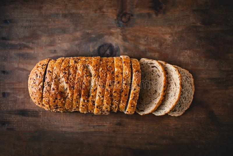 Bästa sikt av skivat wholegrain bröd på mörk ructic träbackg royaltyfria bilder
