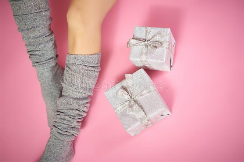 Bästa sikt av slanka kvinnliga ben i varma gråa sockor med xmas-gåvor på en rosa bakgrund royaltyfri foto