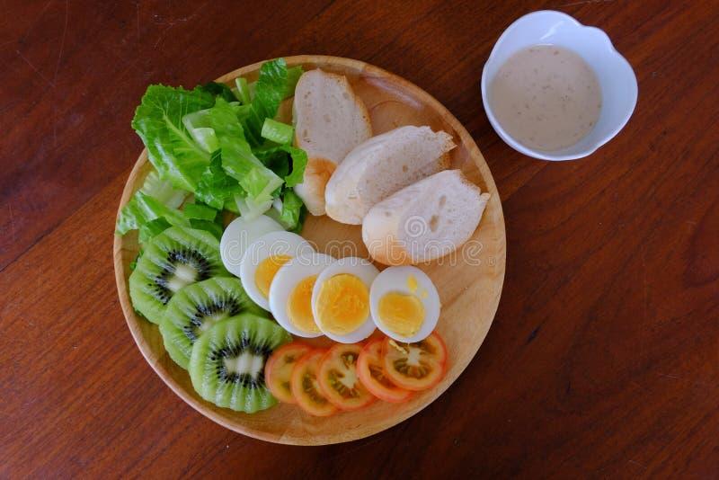 Bästa sikt av Sliced serven för äggsallad med grönsaken, kiwin, tomaten, frasigt bröd och den avskilda japanska sesamdressingen arkivfoton