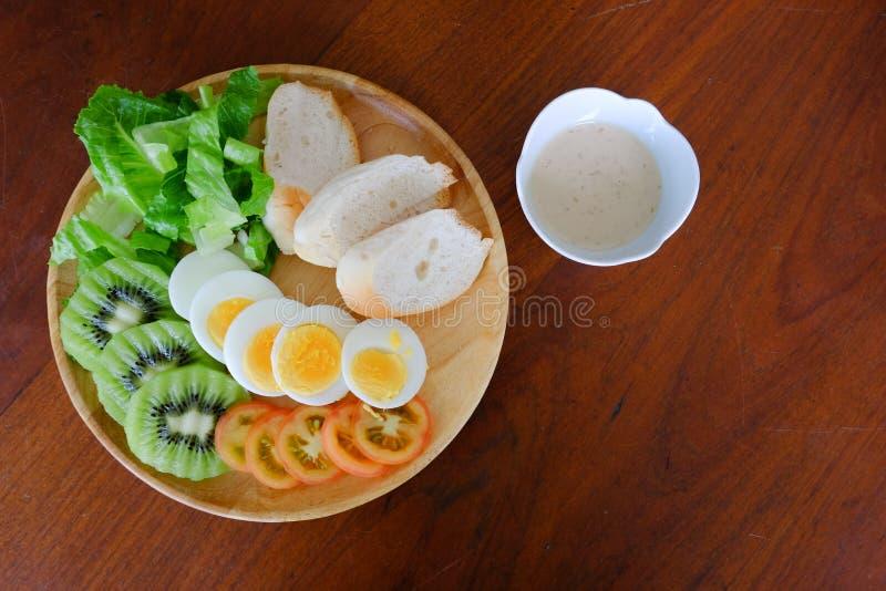 Bästa sikt av Sliced serven för äggsallad med grönsaken, kiwin, tomaten, frasigt bröd och den avskilda sesamdressingen arkivbilder