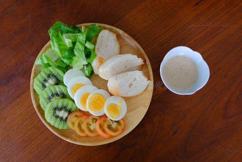 Bästa sikt av Sliced serven för äggsallad med grönsaken, kiwin, tomaten, frasigt bröd och den avskilda sesamdressingen fotografering för bildbyråer