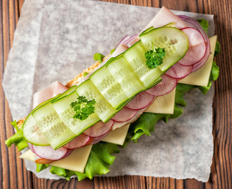 Bästa sikt av smörgåsen med skinka, ost, bacon, rädisa, grönsallat arkivbild