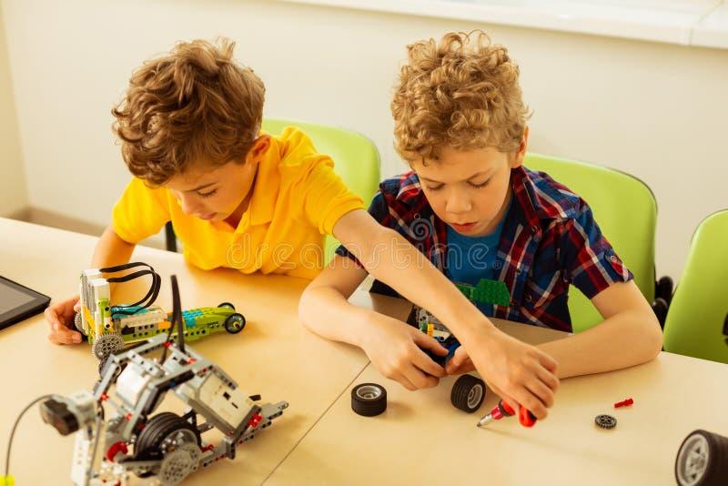 Bästa sikt av smarta trevliga pojkar som konstruerar leksaker royaltyfri foto