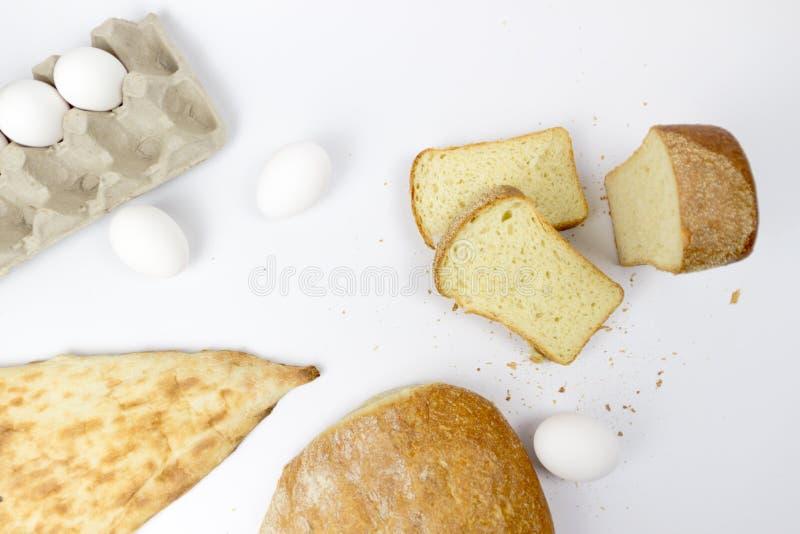 Bästa sikt av sortimentet av den olika sorten av det sädes- bagerit: bröd giffel, bullar som isoleras på vit, woodden bakgrund arkivfoto