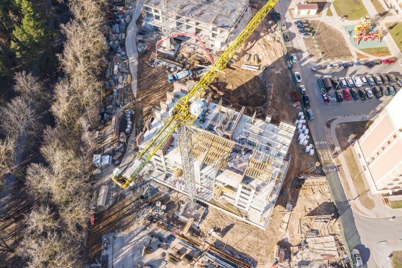 Bästa sikt av stadskonstruktionsplatsen med den höga gula tornkranen Surrfotografi royaltyfri foto