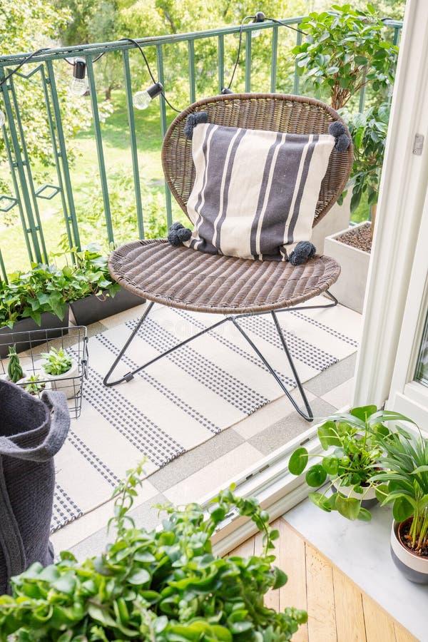 Bästa sikt av stilfull rottingstol på balkongen av det moderna plana verkliga fotoet royaltyfria bilder