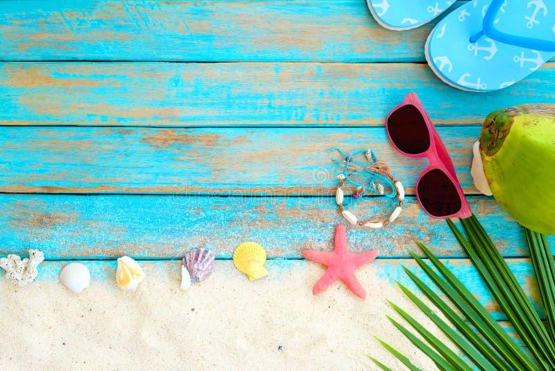 bästa sikt av strandsand med häftklammermataren, kokosnöten, solglasögon, kokosnötsidor, sjöstjärnan, skal, korall och armbandet  arkivbilder