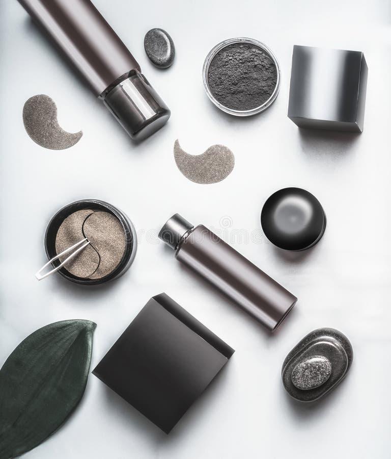 Bästa sikt av svart och brunt förpacka av ansikts- kosmetiska produkter Den moderna kosmetiska uppsättninglägenheten lägger Hudom royaltyfri fotografi