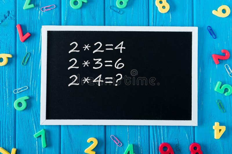 bästa sikt av svart tavla med färgrika nummer för multiplikationstabell och gemmar på blått trä royaltyfri foto