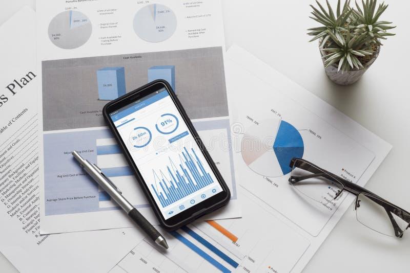 Bästa sikt av tabellen för kontorsskrivbord med grafdiagrammet på den falska övre smartphonen på den vita skrivbordtabellen Affär arkivbilder