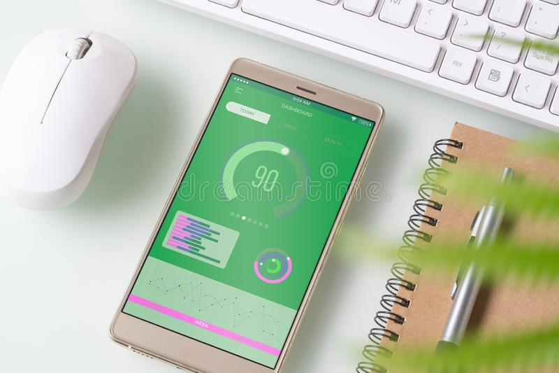 Bästa sikt av tabellen för kontorsskrivbord med grafdiagrammet på den falska övre smartphonen på den vita skrivbordtabellen Rappo royaltyfria foton
