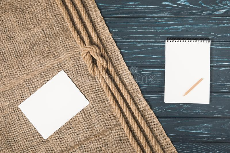 bästa sikt av tomt papper på säckväv med den knöt rep- och mellanrumsläroboken med blyertspennan royaltyfria bilder