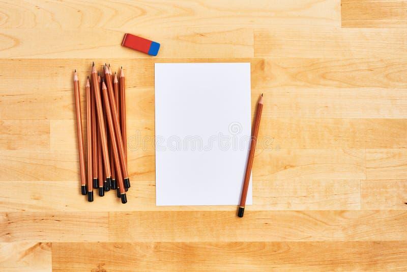Bästa sikt av träkontorsskrivbordet med det tomma arket av papper, radergummit och en grupp av blyertspennor arkivbilder
