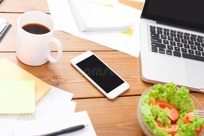 Bästa sikt av träskrivbordet med sallad, bärbara datorn, smartphonen och andra objekt arkivbild