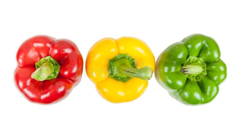 Bästa sikt av tre färgade peppar på vit royaltyfri foto