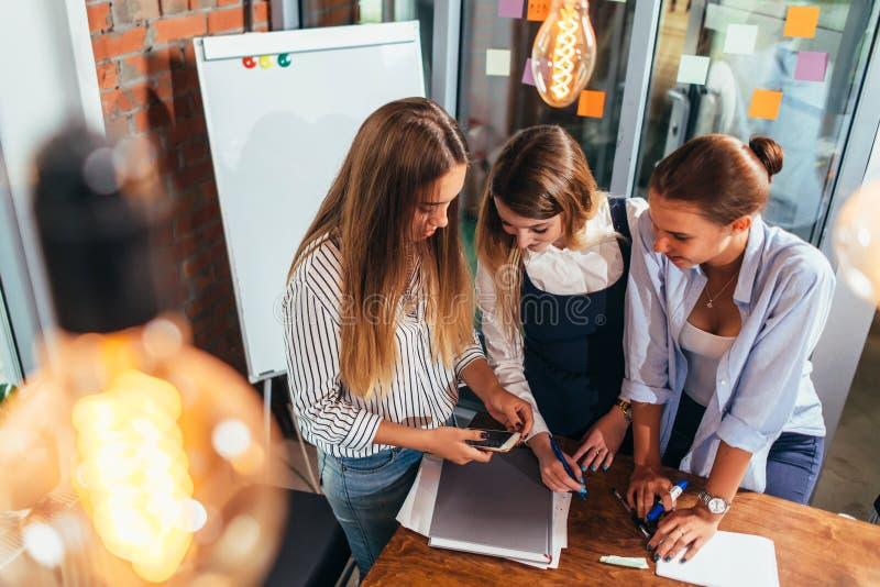 Bästa sikt av tre gladlynta kvinnliga studenter som ser mobiltelefonskärmanseende i klassrum arkivbilder