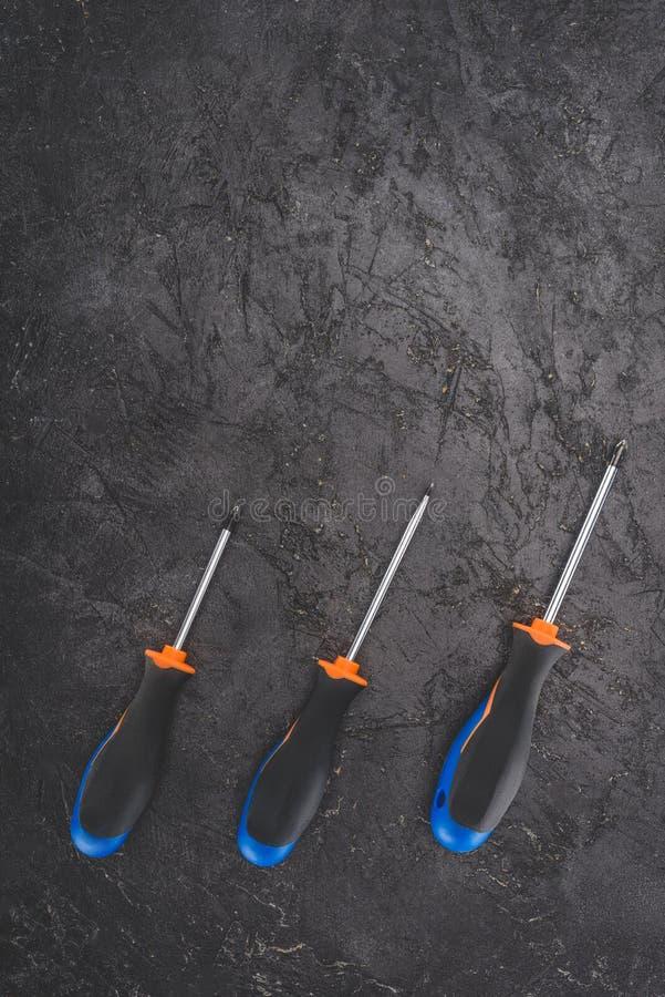 bästa sikt av tre skruvmejslar som förläggas i rad på svart royaltyfri bild