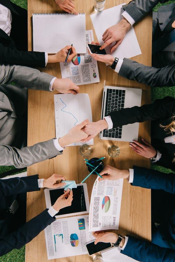 Bästa sikt av två affärspartners som skakar händer medan kollegor som arbetar på tabellen arkivfoton