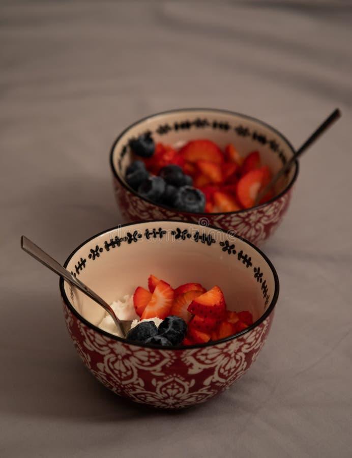 Bästa sikt av två bunkar med yoghurt, jordgubbar och blåbär över gråa ark royaltyfri bild